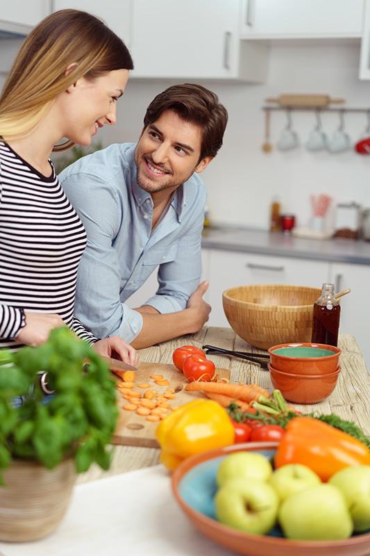 glückliches junges paar kocht zusammen zuhause