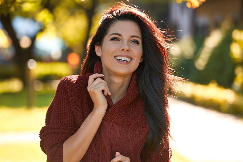 Portrait of beautiful brunette woman in autumn red sweater. Cute